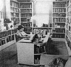 Black and white photo of a woman sitting in her desk surrounded by books