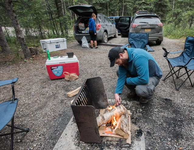 man tending a campfire while a young woman unpacks items from a nearby car