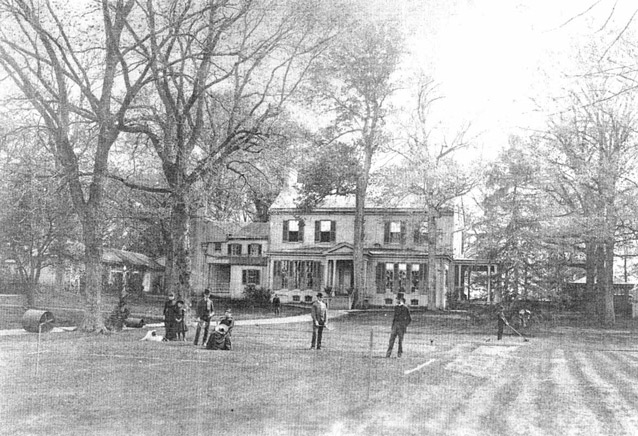 A group of people gather on a lawn in front of a large house in a black and white image.