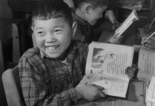 Historic photo of a third grade boy holding a book at the Manzanar War Relocation Center