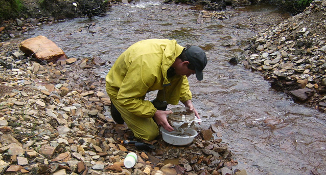 Man collecting sediment in a stream bed