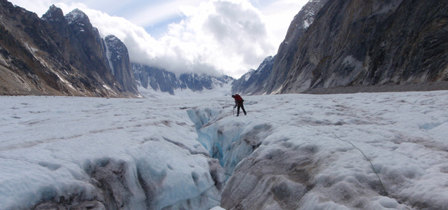 man standing on glacier in mountains