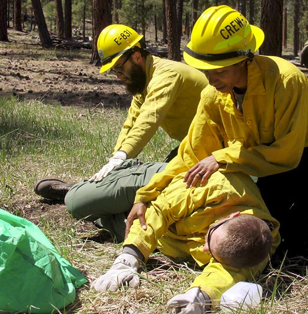 Firefighters assess an unresponsive crew memeber during a simulation