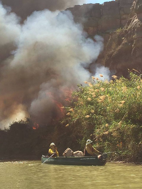 Firefighters reach river cane by boat for ignition during a prescribed burn along the Rio Grande