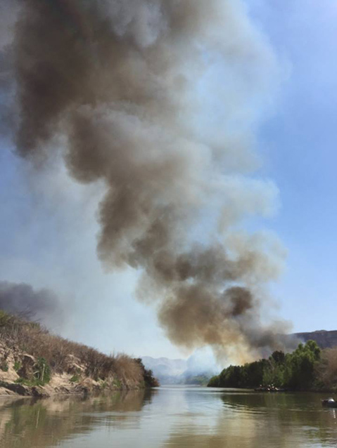 Firefighters canoeing on the Rio Grande during a prescribed burn along the Rio Grande