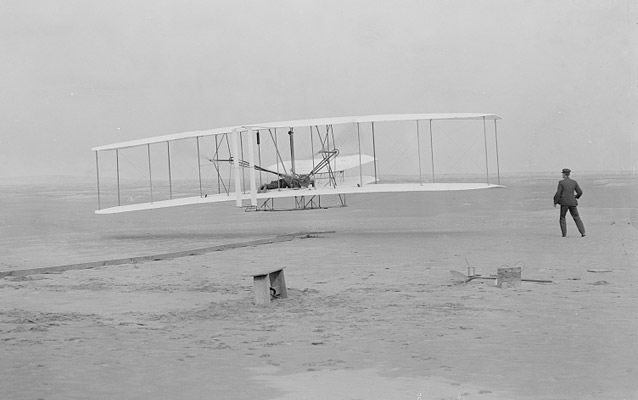 The Wright Flyer lifts off with Orville as pilot, Wilbur is running alongside- Kitty Hawk, 1903