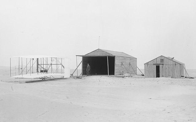 The Wright Flyer next to two camp buildings- Kitty Hawk, 1903