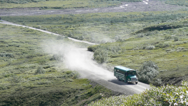 a green bus drives down a gravel road with dust filling the air behind it