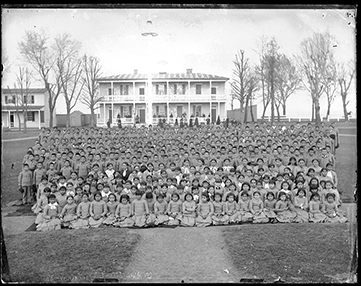 A group of over 100 Native American students standing and facing camera at Carlisle Indian School