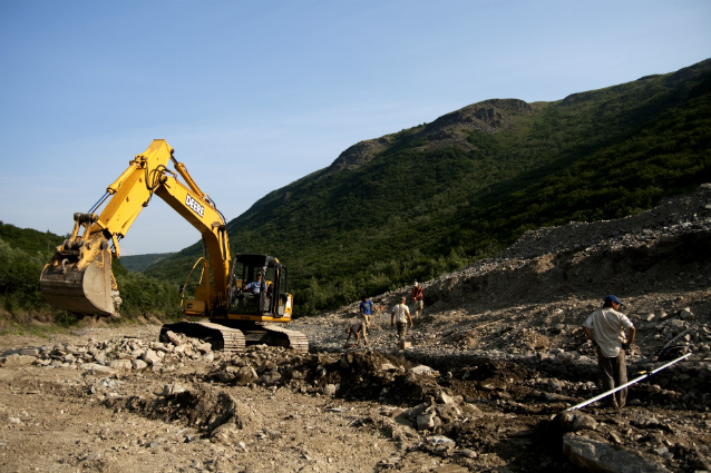 an excavator sits on piles of rocks and gravel