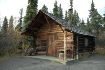 a log cabin in front of spruce trees