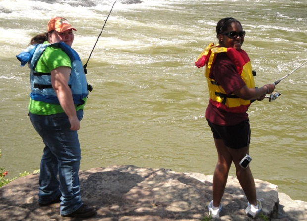 Two girls fishing and wearing life jackets