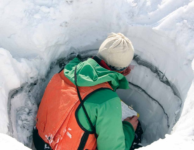 a person sits in in a hole of snow analyzing layers of ash