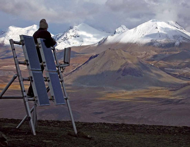 a man stands on solar panels with mountains in the distance