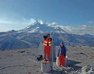 two women stand at the top of a seismic station with a snow-capped volcano in the distance