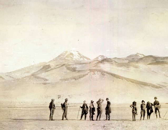 historic photo featuring a group of people with mountains in the distance