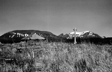 historic photograph of a cross in a field with mountains in the background
