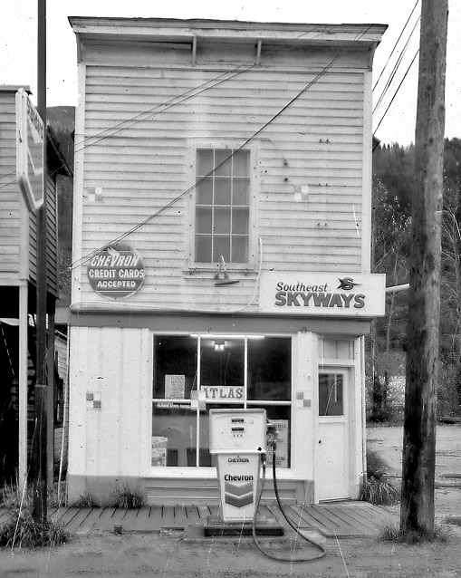 Black and white photo of a building and a gas pump.