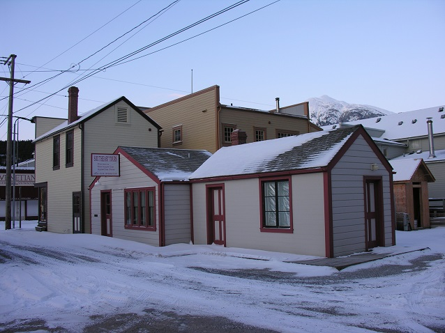 Two small white and red buildings on a snow covered street.