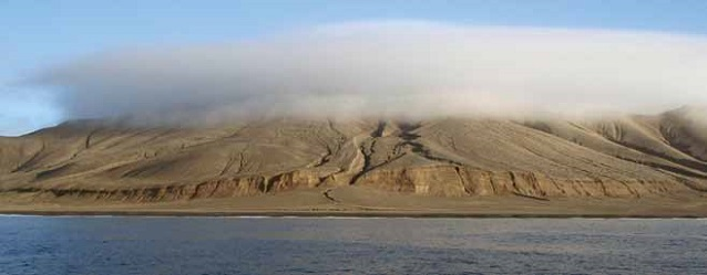 a rocky island covered by a cloud