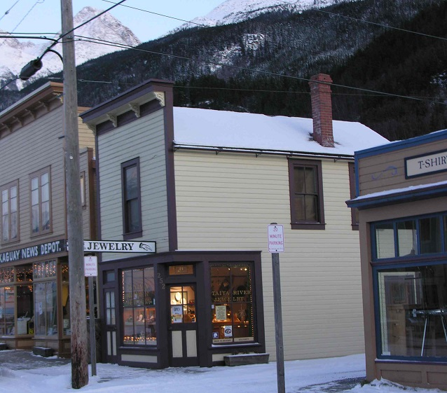 A cream colored building on a snow covered street.