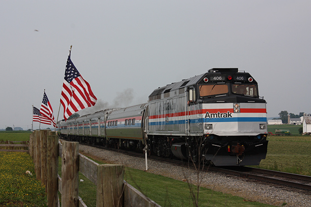 A silver Amtrak train with red, white, and blue stripes moves past a line of American flags.