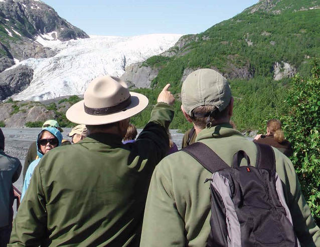 a park ranger next to a visitor points up the mountain with a glacier in the background