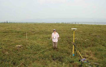 woman stands near ground plots and soil monitoring equipment in the open tundra