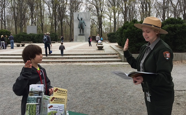 Ranger swearing in a Junior Ranger with a statue of Theodore Roosevelt in the distance