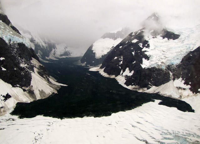 a rock debris field on a large glacier surrounded by snowy mountains