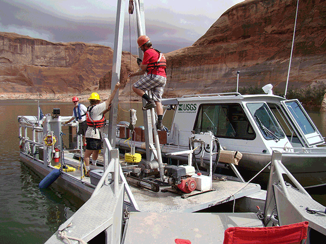 Boat with scientific equipment. people with lifejackets operate equipment.
