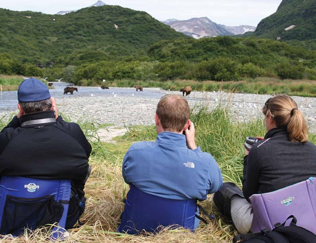 three people sit watching brown bears in the distance