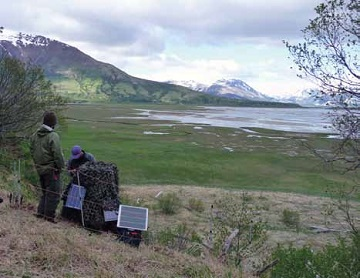 two people install a camera and solar panels with a floodplain and mountains in the distance