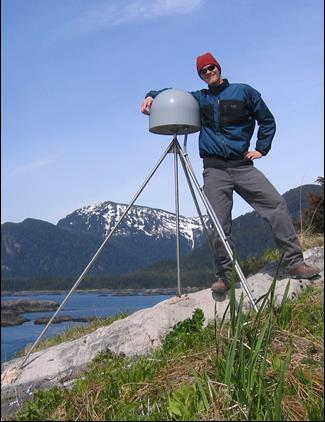man stands next to GPS station on top of a tripod