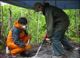 two researchers drill into bedrock to install GPS unit