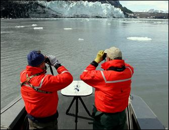 researchers scan the water with binoculars