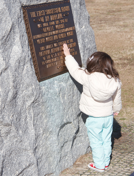 Young girl touching First Flight boulder, 2013