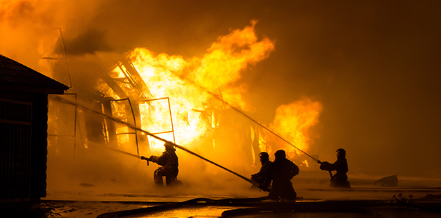 Firefighters putting out a large building fire at night.