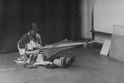 A Zuni Ihamana sitting on the floor weaving