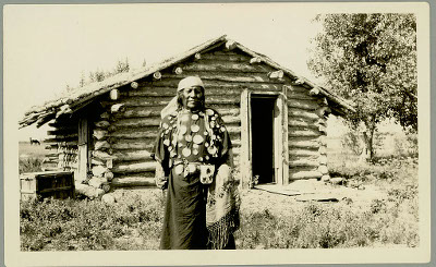 A man standing in front of a small wood cabin
