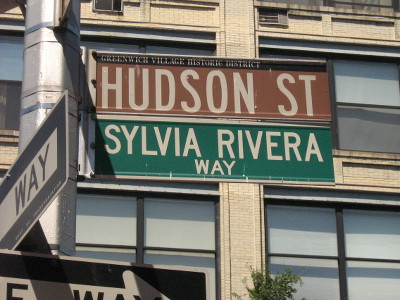 "A street sign that says ""Hudson St."" and ""Sylvia Rivera Way"""