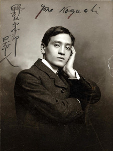 A man in a suit poses with one hand on the side of his face