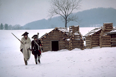 Two Revolutionary War reenactors walk in the snow with a log cabin and trees behind them
