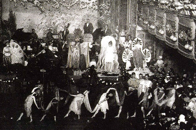 A line of dancers in costumes in front of a stage with a band and performers