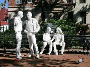 White statues of people in a park, two standing and two sitting on a park bench