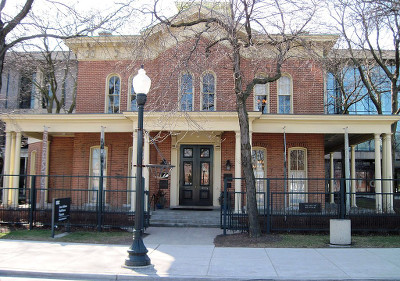 Outside of the Hull House, a two-story brick house with columns