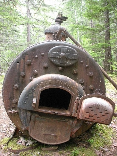 An iron boiler with a door open in a forest.