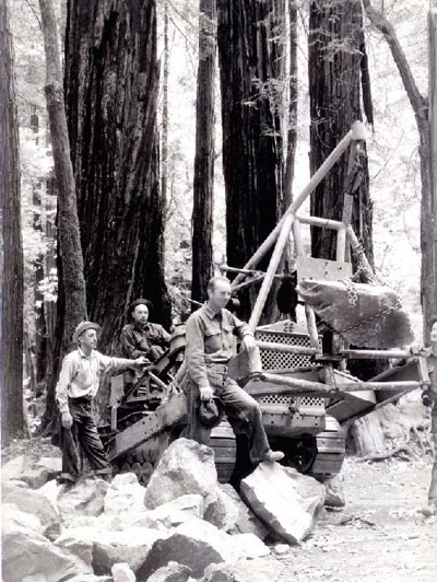Black and white image of people posing with boulders alongside towering coast redwood trees