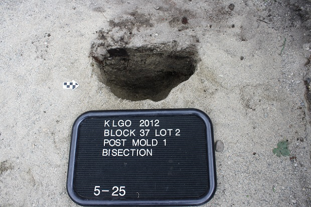 Sandy soil with dark half-circle depression and black and white sign