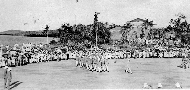 Historical black and white image of troops marching on a parade field